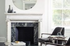 a modern luxurious living room in a monochromatic color scheme, with a fireplace clad with black marble and a white marble mantel