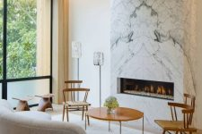 a modern refined living room with a white marble fireplace that warms up the whole space and makes it cozier