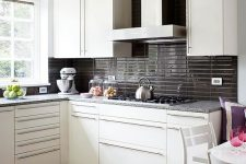 a modern white kitchen with glossy graphite grey stacked tiles and grey stone coutnertops for a contrast