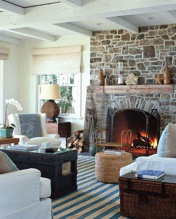 a neutral and chic living room with a stone fireplace that becomes a centerpiece, adds interest and texture to the space