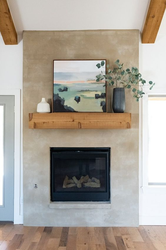 a neutral concrete fireplace with a wooden mantel, an artwork and greenery in a vase looks breezy and chic
