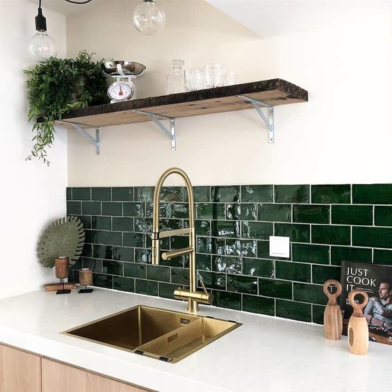 a neutral contemporary kitchen with white countertops and hunter green subway tiles plus gold fixtures for a more elegant look