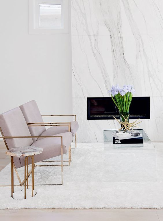 a neutral elegant space with a white marble clad fireplace, lavender chairs and touches of brass for more chic