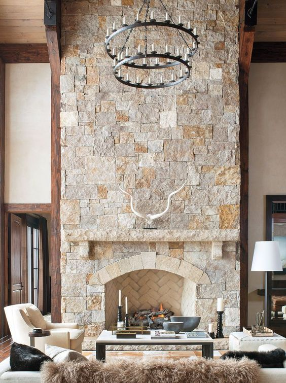 a neutral farmhouse living room with a stone fireplace, elegant creamy furniture and a statement chandelier