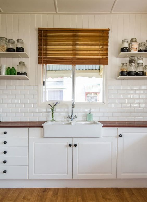 a neutral kitchen with farmhouse touches, rich stained wooden countertops and a white subway tile backsplash