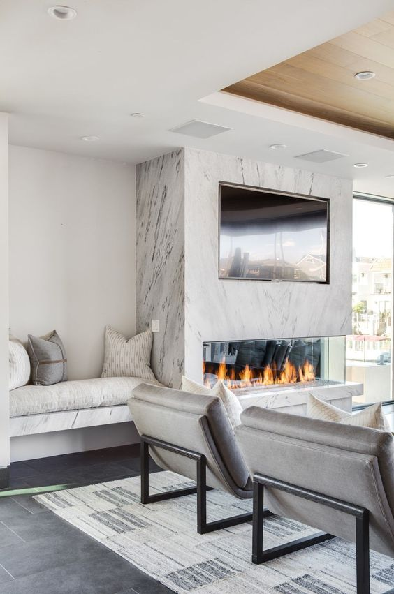 a neutral living room with a marble fireplace and a TV over that is a real centerpiece of the whole space