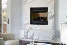 a neutral luxurious living room with a marble clad built-in fireplace and refined leather and velvet furniture
