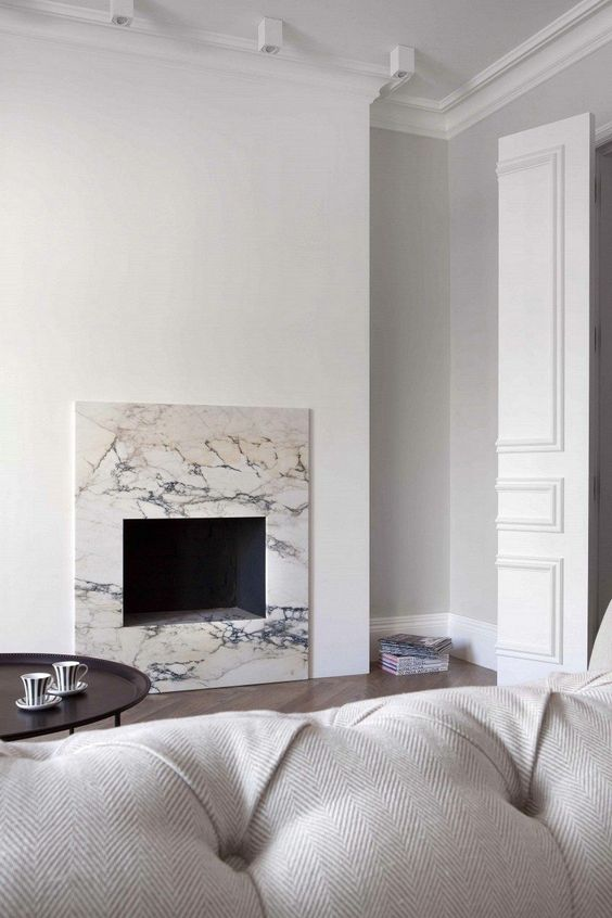 a neutral minimalist living room with a non-working fireplace clad with white marble for a chic and cool touch