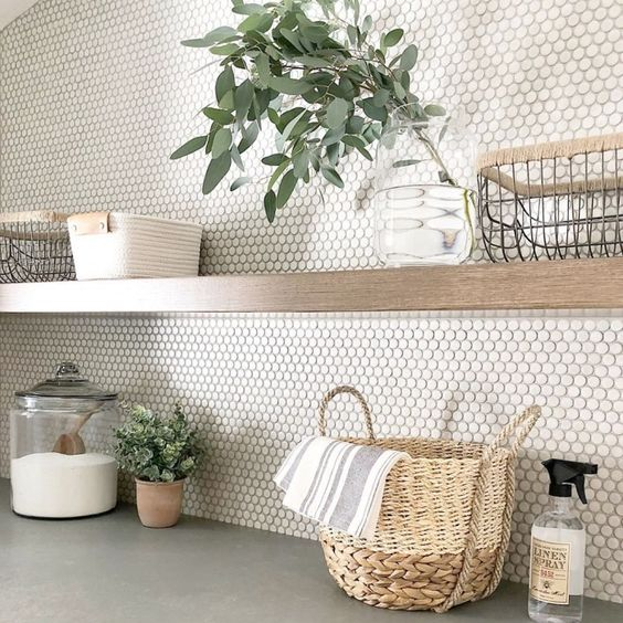 a neutral penny tile backsplash and a wooden open shelf plus lots of greenery for a cozy farmhouse look