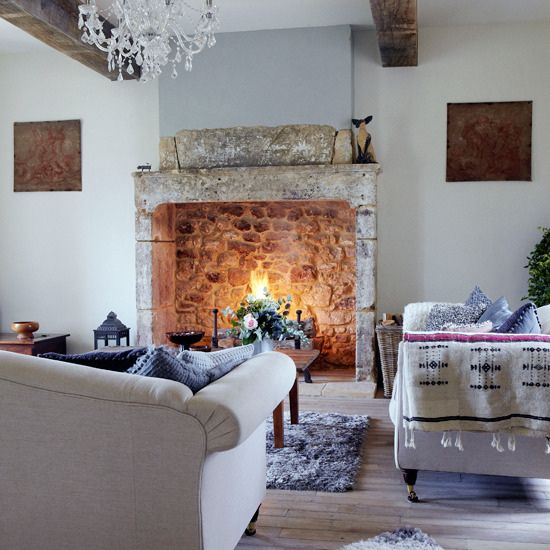 a neutral refined living room with a large vintage hearth of stone and some firewood and a lantern inside for more coziness