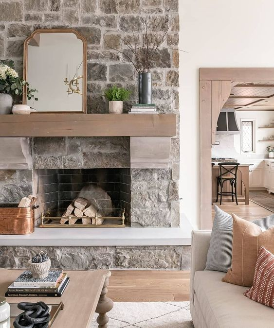 a neutral rough stone fireplace with firewood on a gold stand, a tan mantel with potted plants and a mirror on it