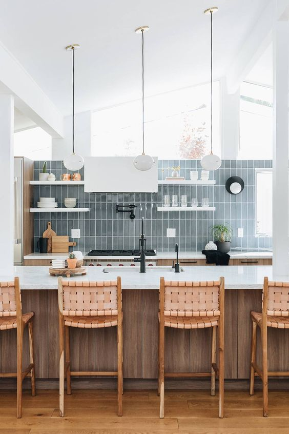 a neutral stained wooden kitchen, white shelves and a hood, a blue stacked tile wall and pendant lamps