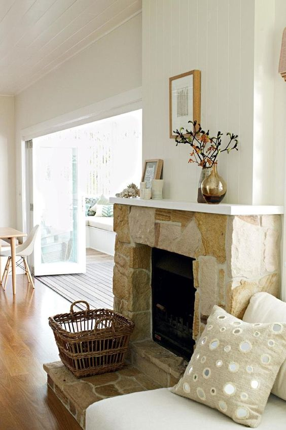 a neutral stone fireplace with a basket for firewood and a white mantel with candles, vases and blooms makes the space cozy and chic