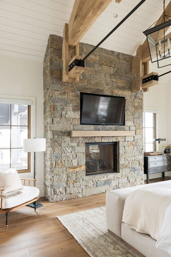 a ranch bedroom done with a rough stone fireplace with a wooden mantel matching the beams is a lovely and welcoming space