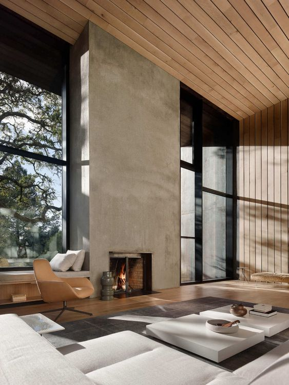 a refined minimalist living room with a concrete fireplace, neutral furniture, wooden walls and ceiling plus glazed walls