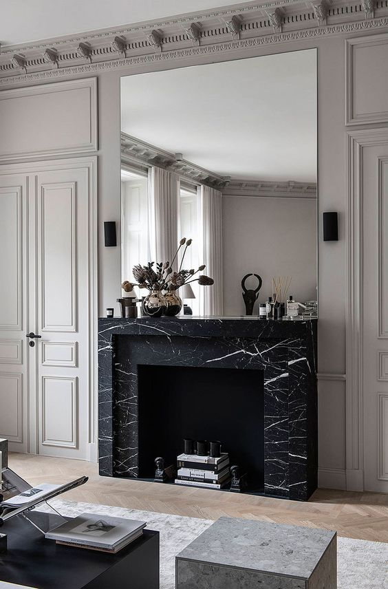 a refined monochromatic living room with a non-working fireplace clad with black marble and an oversized mirror over it