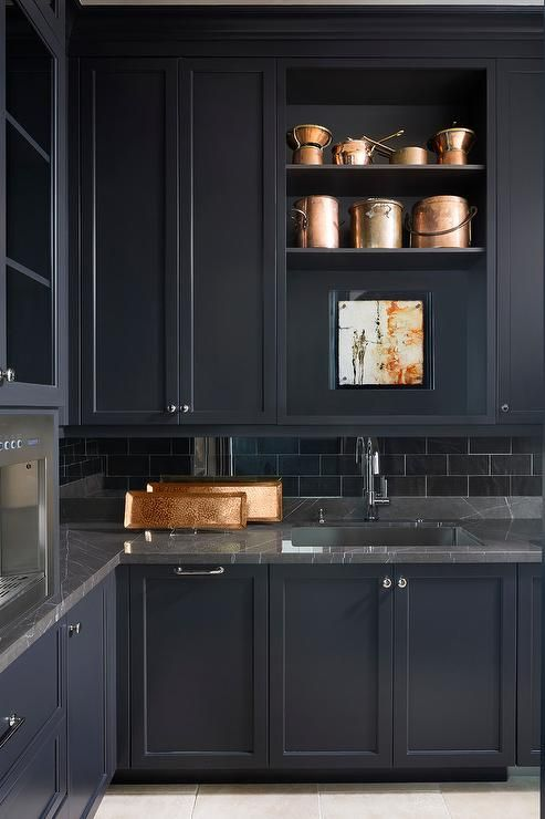 a refined moody kitchen in black, with grey marble countertops and a black subway tile backsplash is ultimately chic