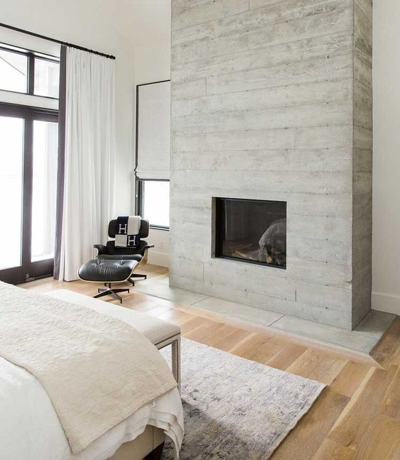 a refined neutral bedroom with a concrete fireplace that matches the color scheme and cozies up the space