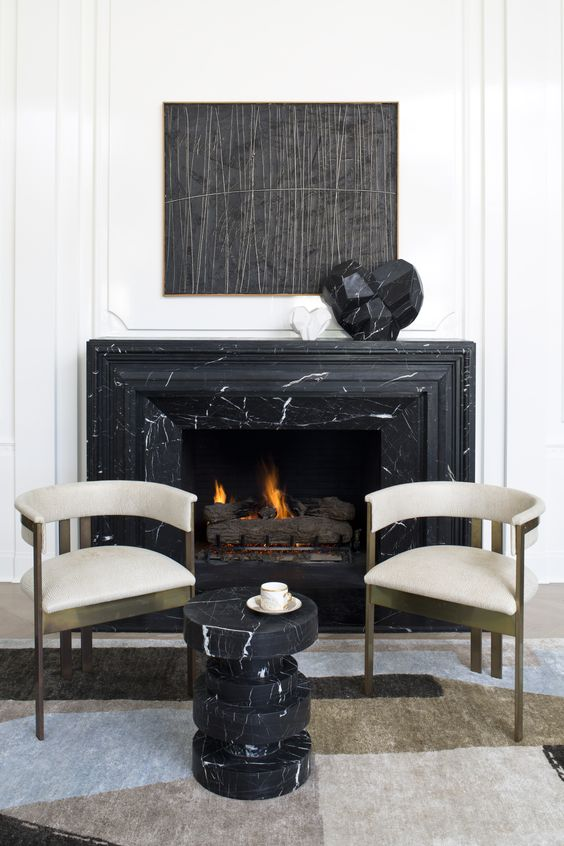 a refined nook with a black marble fireplace and a matching side table, gorgeous brass and velvet chairs