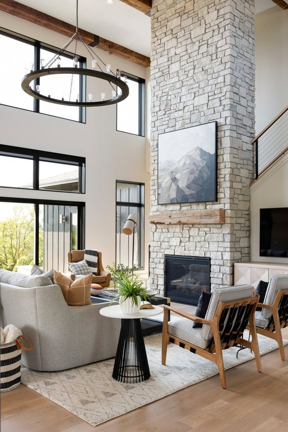 a refined ranch living room with a stone fireplace, wooden mantel and an artwork plus chic grey furniture