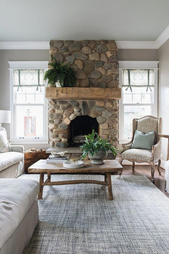 a refined vintage living room with a river rock fireplace that brings a touch of nature to the space