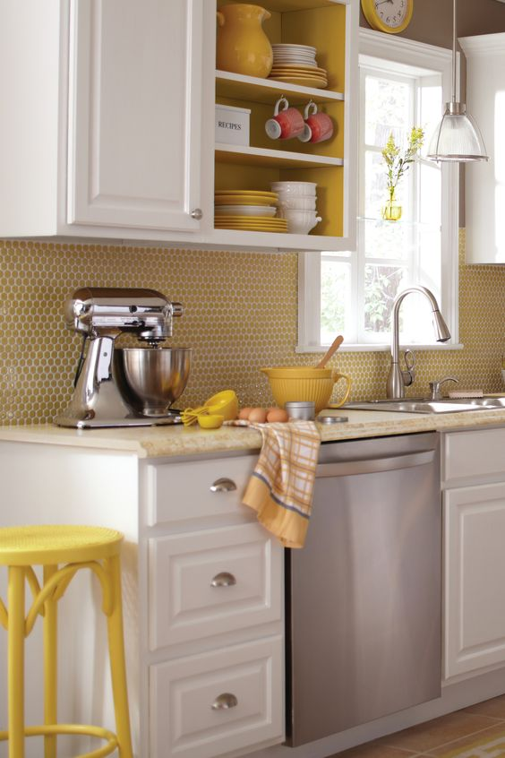 a retro inspired kitchen with white cabinets, a yellow penny tile backsplash and yellow painted niches