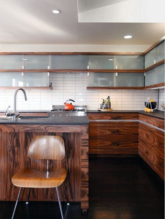 a rich stained wooden kitchen with frosted glass cabinets and a white stacked tile backsplash is very bold