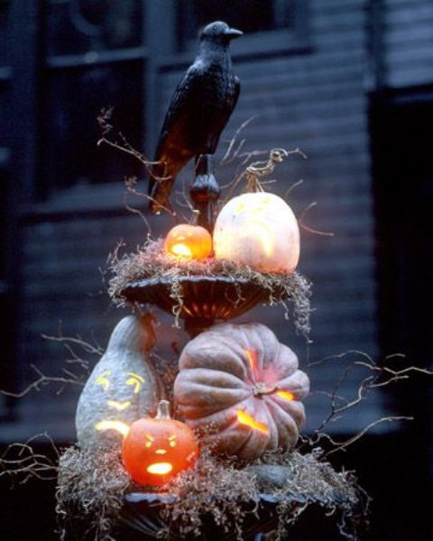 a rustic Halloween decoration of a stand with moss, branches, pumpkins and a large blackbird is very scary