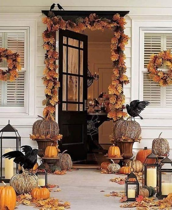 a rustic Halloween porch with fall leaves, faux and vine pumpkins, candle lanterns and blackbirds is very cool