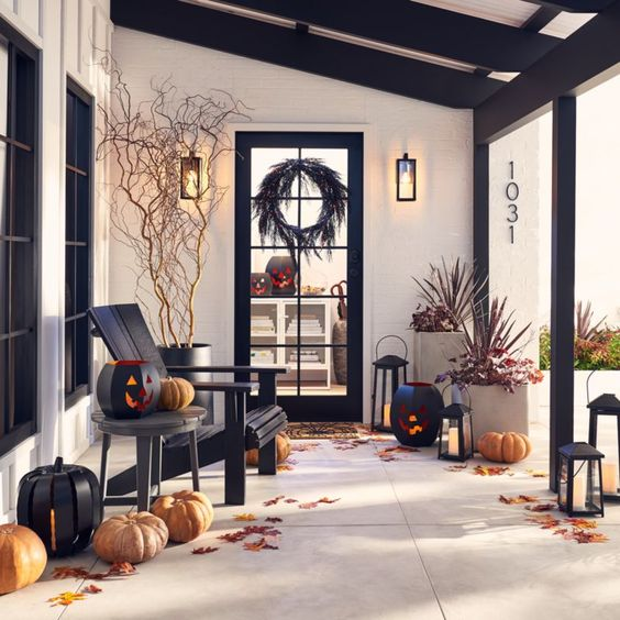 a rustic Halloween porch with lots of leaves, natural pumpkins, wooden black pumpkin lanterns and dried and fresh plants