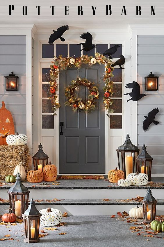 a rustic Halloween porch with paper blackbirds, a fall leaf and veggie garland and wreath, laser cut pumpkins, laeaves and candle lanterns