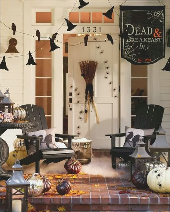 a rustic Halloween porch with witches' hats, natural pumpkins, candle lanterns, a broom and cool pillows