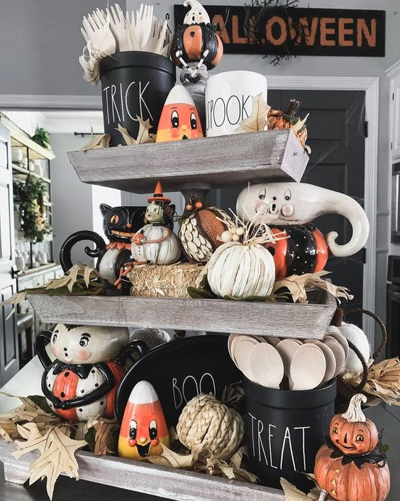 a rustic Halloween stand with hay, pumpkins, husks, vintage toys and fall leaves and other bright stuff