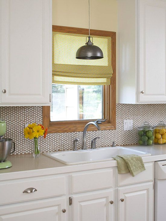 a rustic white kitchen with neutral stone countertops, neutral penny tiles with a tan backing and bright touches