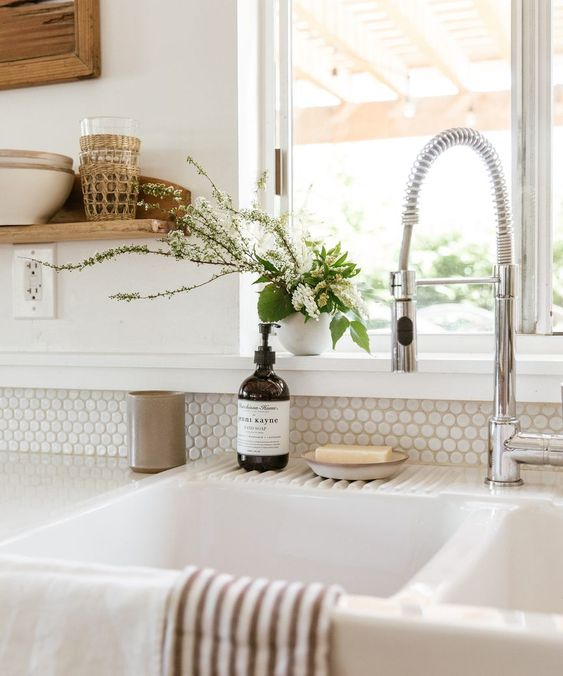 a serene neutral kitchen with white penny tiles and white stone countertops to make the space more interesting