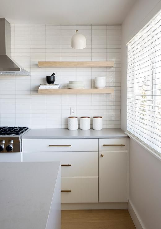 a serene white kitchen with a stacked tile wall, creamy cabinets, open shelves and brass fixtures for more chic