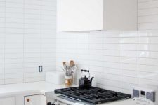 a serene white kitchen with a white stacked tile backsplash, copper fixtures and a white hood is very welcoming
