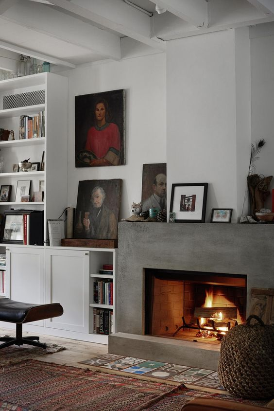 a sophisticated living room with a concrete fireplace and lots of artworks and books around it is welcoming