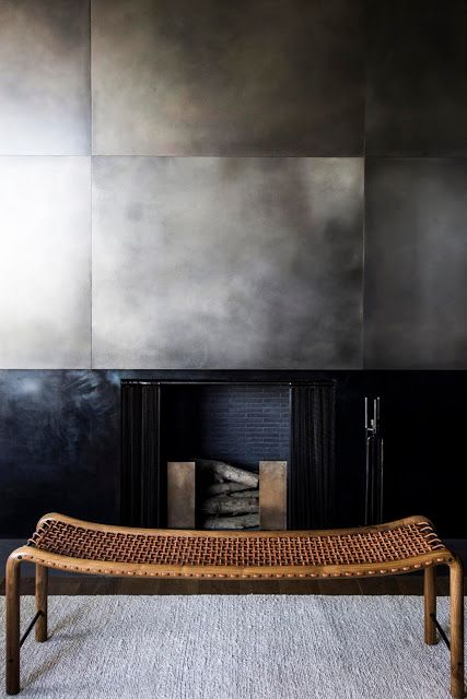 a statement fireplace with sleek and shiny metal sheets that surround it and a woven bench in front of it is a gorgeous idea