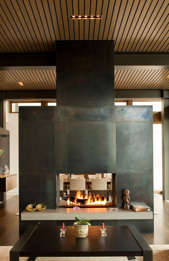 a stunning two-sided fireplace clad with metal sheets to separate the living and dining room and give coziness to both