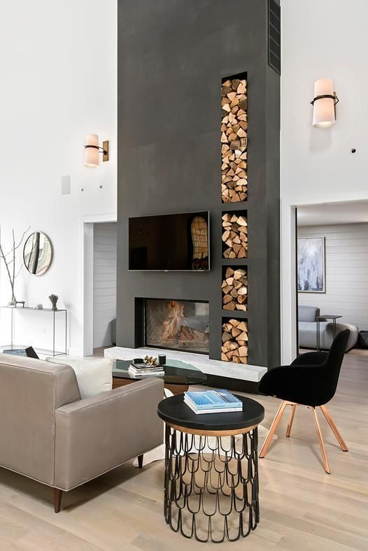 a stylish contemporary living room with a graphite grey concrete fireplace and niches for storage plus chic and stylish furniture