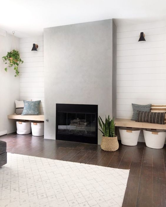 a stylish laconic living room with a concrete fireplace and benches on each side, pillows and baskets for storage