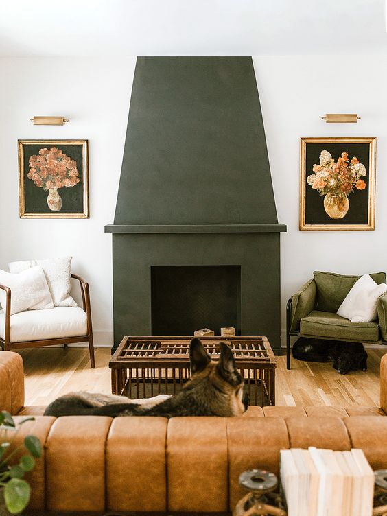 a stylish mid-century modern living room with a black concrete fireplace, a leather sofa and white and green chair