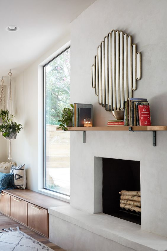 a stylish modern concrete fireplace with a mantel with books and a catchy mirror over it plus a bench next to it