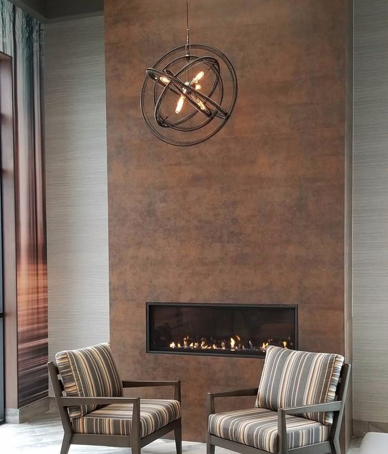 a stylish modern living room with a built-in fireplace clad with copper and a metal sphere chandelier looks very cool