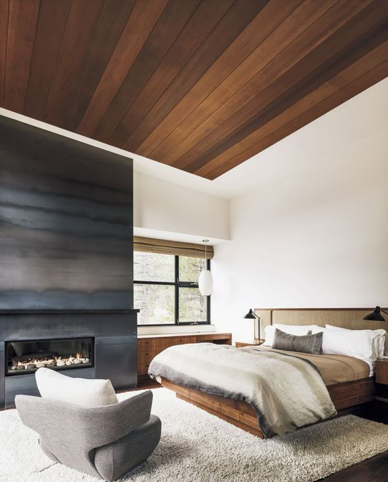a sytlish contemporary bedroom with a large built-in fireplace surrounded with grey steel sheets for a slight chalet feel
