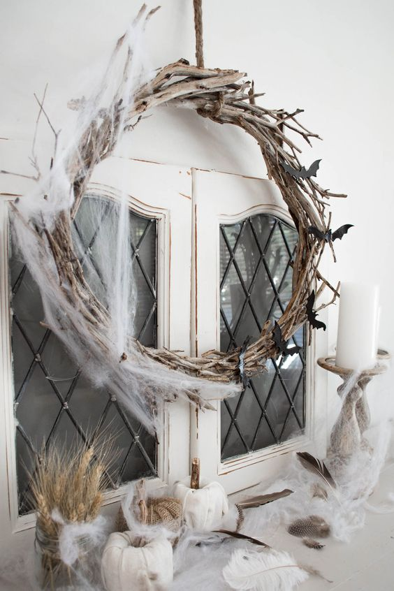 a twig and stick Halloween wreath with spiderweb, fabric pumpkins with feathers and candles