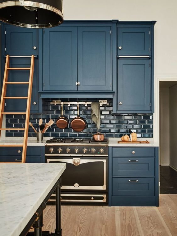 a vintage-inspired navy kitchen with glossy navy subway tiles, white marble countertops and metallic touches