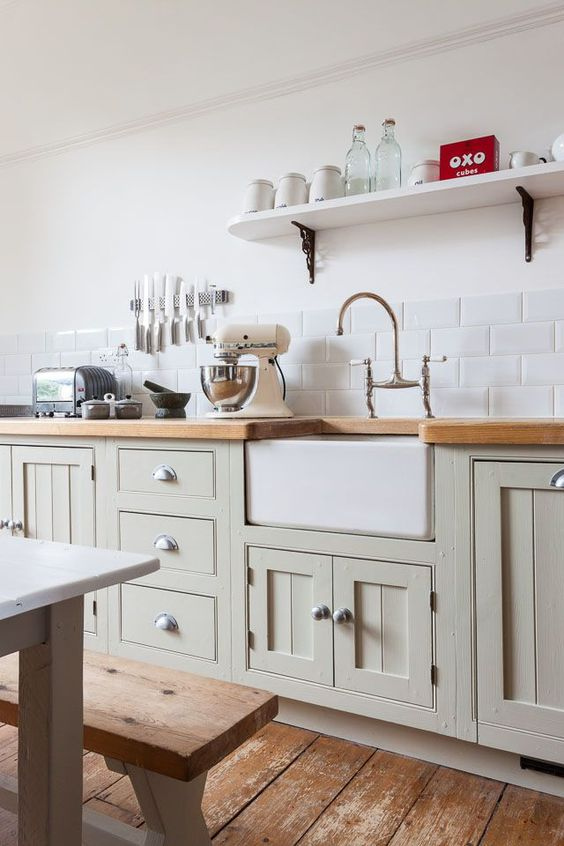 a vintage light green kitchen with large scale subway tiles, wooden countertops and a traditional dining set with benches for a countryside feel