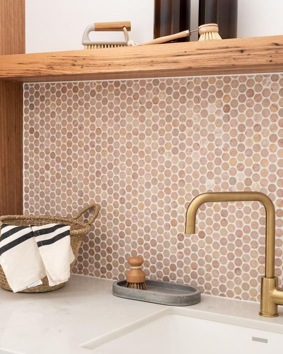 a warm terracotta penny tile backsplash matches the wood and a brass faucet and brings a cozy feel